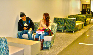 Two students laughing while sitting in Sutter County Lobby