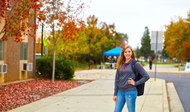 Student at bus stop on Yuba College campus